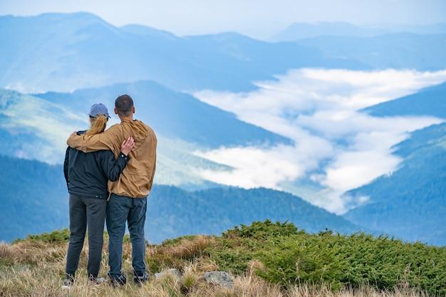 Kobieta i mężczyzna stojący na tle górskiego krajobrazu