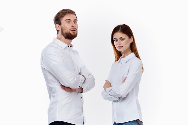 Kobieta i mężczyzna w białych koszulach stoją obok siebie ze skrzyżowanymi rękami