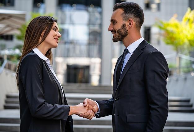 Kobieta i mężczyzna w garniturach uścisk dłoni w pobliżu centrum biznesowego