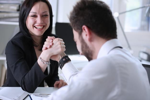Kobieta i mężczyzna w garniturze trzymać ręce w zmaganiu