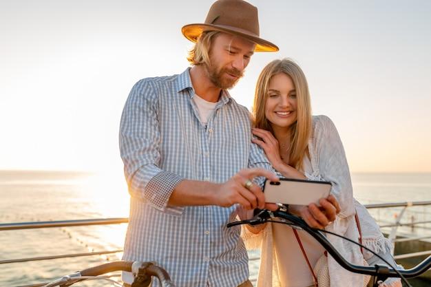 Kobieta i mężczyzna w miłości, podróżowanie na rowerach na morzu zachód słońca