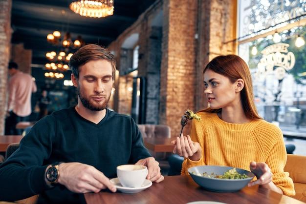 Kobieta i mężczyzna w restauracji sałatka posiłek jedzenie filiżanka kawy