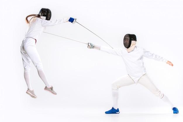 Kobieta i mężczyzna w szermierce, ćwiczący mieczem na szaro