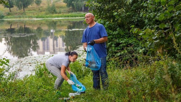 Kobieta i mężczyzna wolontariusz sprząta śmieci na wysypisku w przyrodzie. zdjęcie poziome
