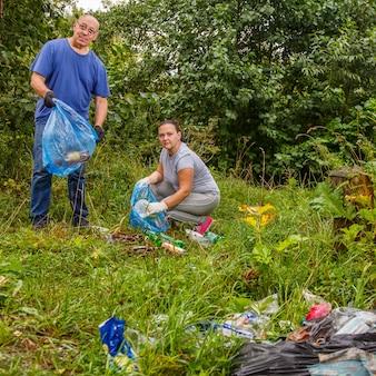 Kobieta i mężczyzna wolontariusze wywożą śmieci z zielonego wysypiska.