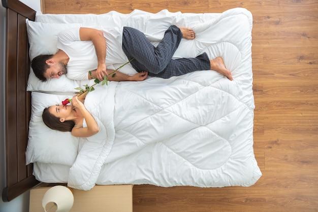 Kobieta i mężczyzna z różą leżą na łóżku. widok z góry