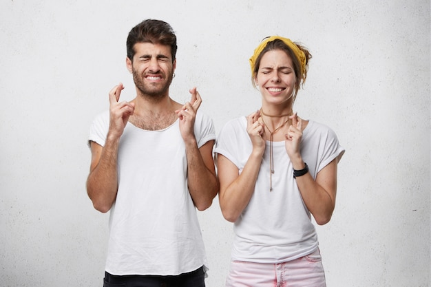 Kobieta i mężczyzna zamykają oczy i trzymają kciuki z nadzieją w oczekiwaniu na ważne wieści