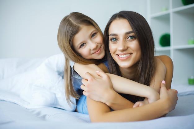 Kobieta i młoda dziewczyna leżąc w łóżku uśmiechnięty