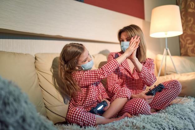 Kobieta i młoda dziewczyna w piżamie i medycznych maskach ochronnych siedząca na kanapie w salonie z kontrolerami gier wideo w domu, automatyczna kwarantanna izolacji, covid-19.