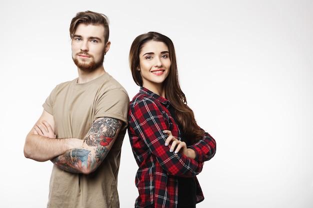 Kobieta i młody mężczyzna stojący z powrotem patrząc prosto.