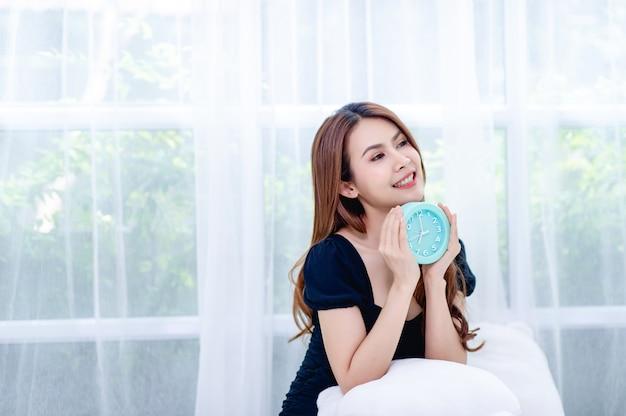 Kobieta i niebieski budzik w sypialni relaks