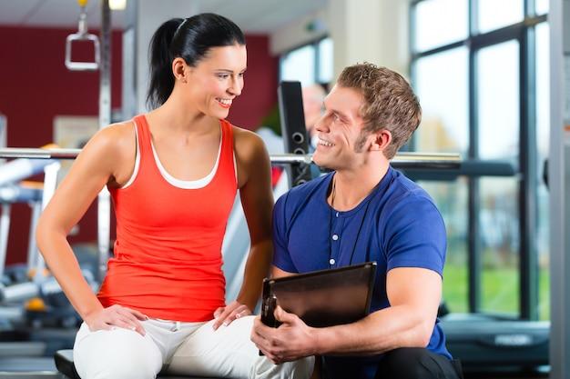 Kobieta i osobisty trener w siłowni fitness