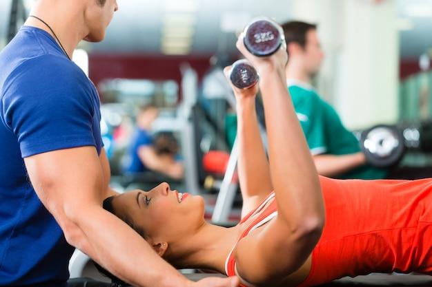 Kobieta i osobisty trener w siłowni z hantlami