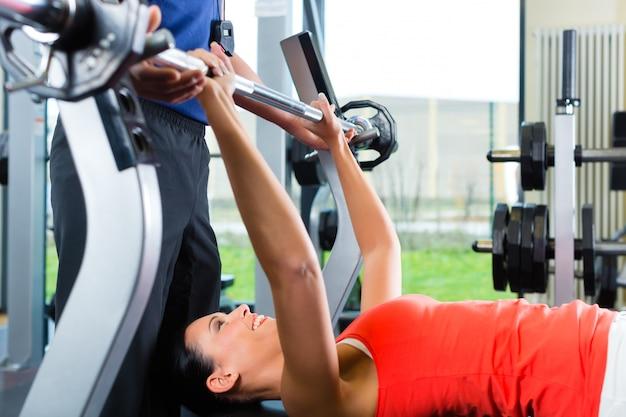 Kobieta i osobisty trener w siłowni