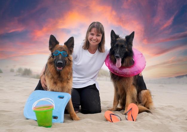 Kobieta i owczarki niemieckie zostają na plaży