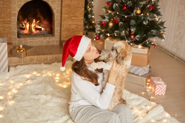 Kobieta i pies bawią się w święta, siedzą na podłodze na miękkiej karafce, pani chce pocałować psa, pozuje w przytulnym salonie z choinką i kominkiem, dziewczynka czapka świętego mikołaja.