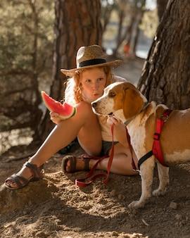 Kobieta i pies jedzący kawałek arbuza