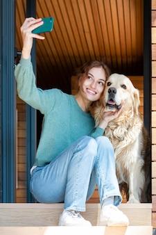 Kobieta i pies przy selfie pełny strzał