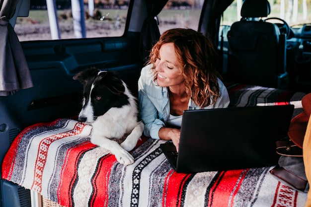 Kobieta i pies rasy border collie w furgonetce. kobieta pracuje na laptopie. koncepcja podróży i technologii