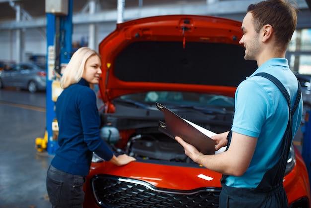 Kobieta i pracownik z listą kontrolną, serwis samochodowy. kobieta klient na automatycznej stacji. sprawdzenie i przeglądy samochodów, profesjonalna diagnostyka i naprawa