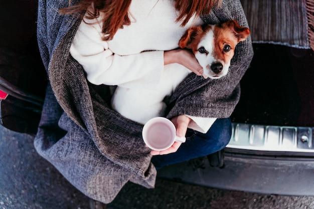 Kobieta i śliczny jack russell pies cieszący się outdoors przy górą w samochód. koncepcja podróży. sezon zimowy. widok z góry