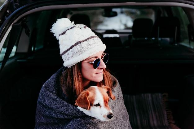 Kobieta i śliczny jack russell pies cieszący się outdoors przy górą w samochód. koncepcja podróży. sezon zimowy
