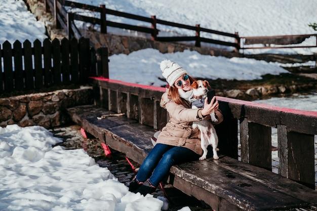 Kobieta i śliczny jack russell pies cieszy się outdoors przy górą z śniegiem. sezon zimowy. kobieta biorąc autoportret z telefonu komórkowego