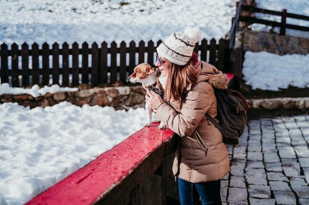 Kobieta i śliczny jack russell pies cieszy się outdoors przy górą z śniegiem. sezon zimowy