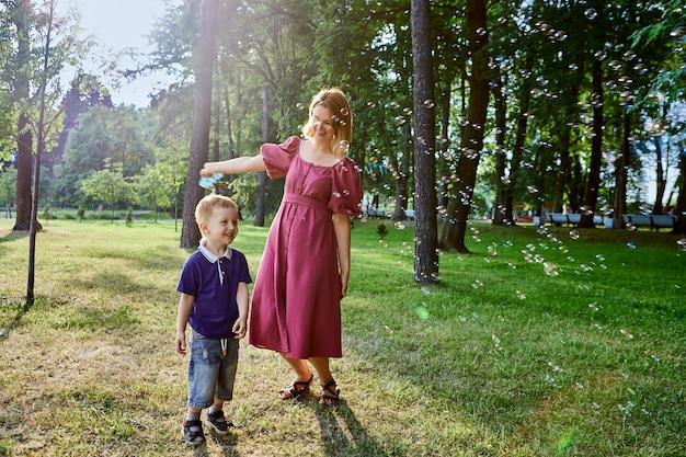 Kobieta i synek bawią się bąbelkami i śmieją się na zewnątrz