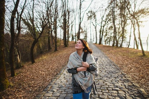 Kobieta idąc kamienną drogą w lesie jesienią.