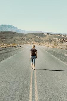 Kobieta idąca boso po pustej drodze w dolinie śmierci