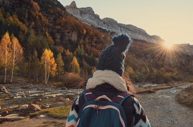 Kobieta idąca obok rzeki w górach. osoba wędrująca po lesie jesienią. park przyrody ordesa y monte perdido w pirenejach