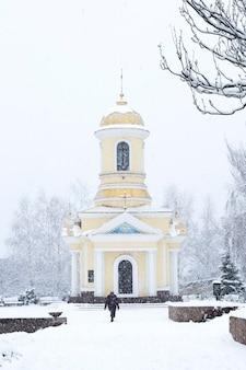 Kobieta idzie do chrześcijańskiej kaplicy pod śniegiem w mieście podczas zamieci.