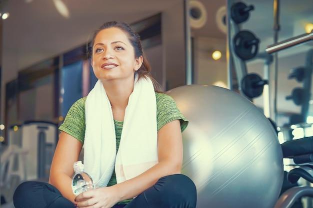 Kobieta idzie do picia wody z plastikowej butelki po treningu.