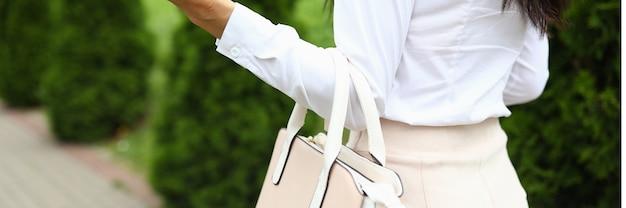 Kobieta idzie i trzyma w dłoni skórzaną beżową torbę. modna i stylowa koncepcja stylu życia.