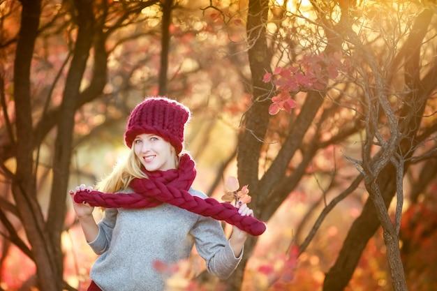 Kobieta idzie jesienią w publicznym parku w ciepłej czapce i czerwonym szaliku