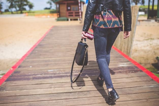 Kobieta idzie na plażę z mostem
