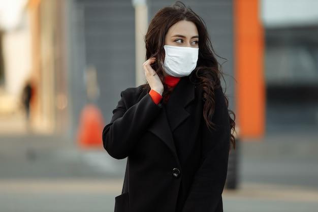 Kobieta idzie na ulicy w masce ochronnej