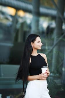 Kobieta idzie na ulicy z zabrać kawę