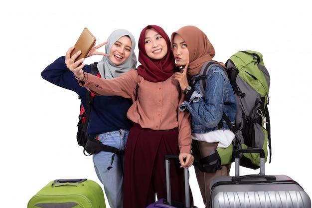 Kobieta idzie na urlop, trzymając walizkę wziąć selfie