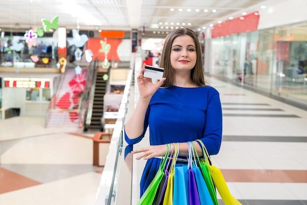 Kobieta idzie na zakupy z kartą kredytową w centrum handlowym