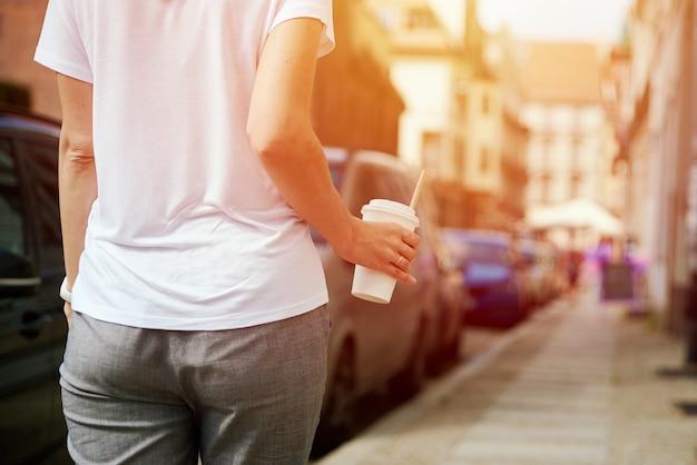 Kobieta idzie ulicą miasta z papierową filiżanką kawy