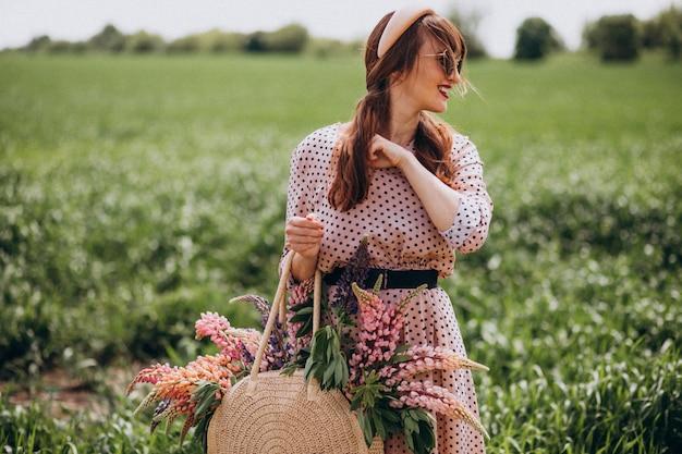 Kobieta idzie w polu z lupinuses