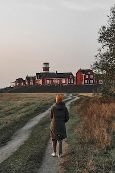 Kobieta idzie wiejską drogą, na jej końcu czerwona i biała latarnia morska. podróż, świt.