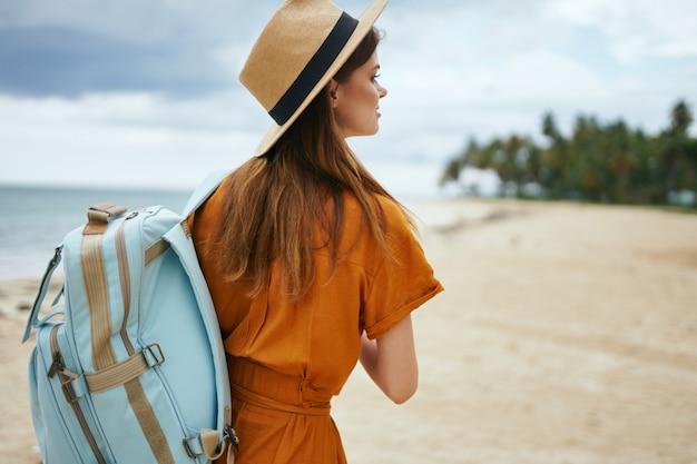 Kobieta idzie wzdłuż oceanu wzdłuż piasku z palmami