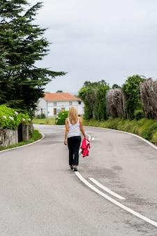 Kobieta idzie wzdłuż zielonej drogi z domem