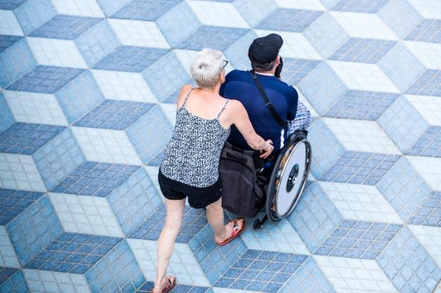 Kobieta idzie z niepełnosprawnym mężczyzną na wózku inwalidzkim, zrelaksowany spacer o zachodzie słońca