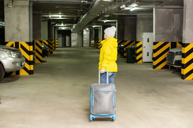 Kobieta idzie z torbą na parkingu podziemnym