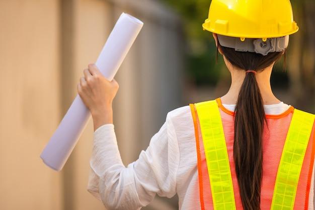 Kobieta inspektora kask ochronny kombinezon gospodarstwa plan inspekcji budynku budowy osiedla, kobieta pracująca