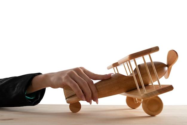 Kobieta interesu bawić się drewnianym samolotem zabawki. koncepcja uruchomienia firmy i sukcesu biznesowego. pojedynczo na białym tle